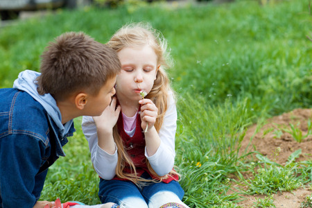 girl and boy blow on dandelion Standard-Bild