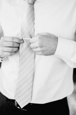 The man put on his shirt and straightens cufflinks. The groom fasten cufflinks on the cuffs of the shirt. The businessman fasten cufflinks on the cuffs of the shirt. Concept successful businessman. 版權商用圖片