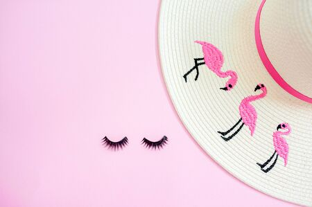 Creative layout made of white painted sunglasses and eyelashes on pastel pink background. Minimal flat lay.