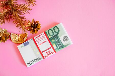Christmas, money on a pink background near Christmas attributes