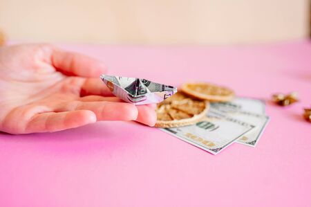boat made of dollar on a pink background, golden grains of coffee