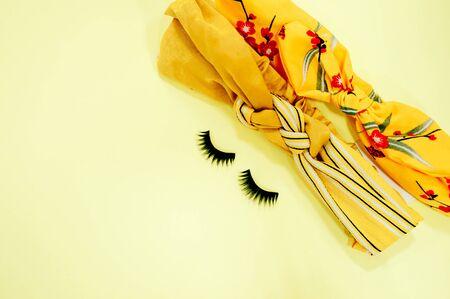 False eyelashes on a yellow background, female accessories flat lay Stock fotó