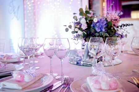 schöne Dekoration und festliche Tischdekoration, beleuchtet durch das Licht mehrfarbiger Glühbirnen