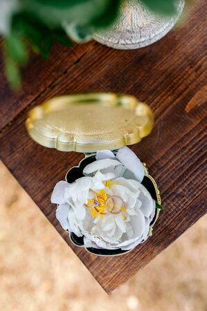 wedding rings, 3 gold rings, in a beautiful golden box on a wooden background Stock fotó