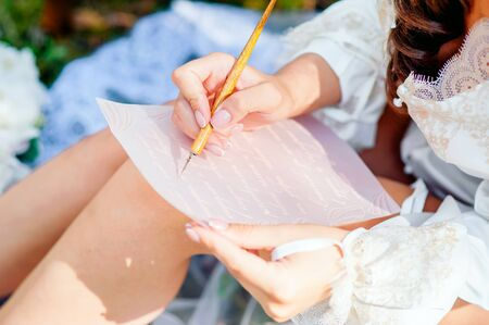 girl writes a love letter in nature with a pen Stock fotó - 129920374