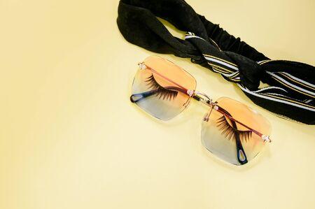 Flat lay of eyelashes and leaf on yellow background. Stock fotó