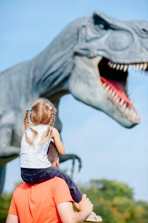 girl on dads shoulders looks at a giant dinosaur in an amusement park