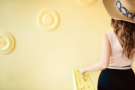 Hello Summer. Summer holidays, vacation and travel concept. Suitcase or luggage bag on yellow background