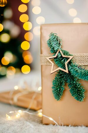 New Year's gift lies on the background of lights under the tree. New Year's and Christmas. Wrapped Gifts