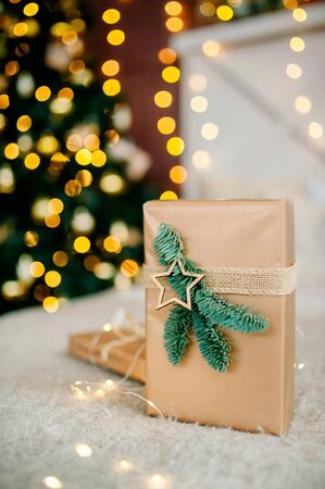 New Years gift lies on the background of lights under the tree. New Years and Christmas. Wrapped Gifts