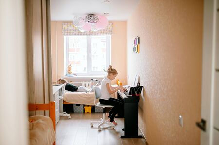girl musician plays the classic digital piano at home during an online lesson, younger brothers play on the bed, social distance during quarantine, self-isolation, the concept of online education 스톡 콘텐츠