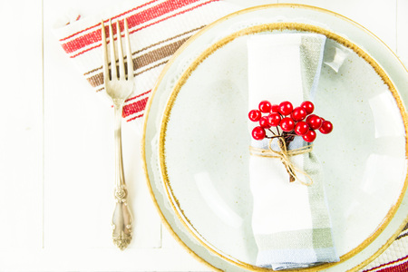 a table setting for Christmas with a viburnum on a plate and an ornament from a Christmas wreath with candles