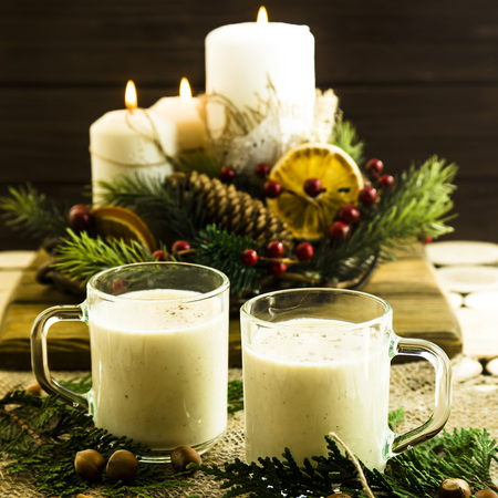 hot milk alcoholic drink   Egg-nog next to the Christmas candle and candles