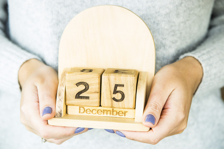 december 25: woman holding a wooden calendar with the date of Catholic Christmas - December 25