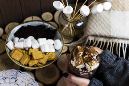 a cup of cocoa with marshmallow on a wooden table next to a rug and sweets Stock Photo