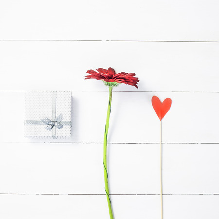 St. Valentines Day concept. A gift, a red dahlia flower and a paper heart on a stick Stock Photo
