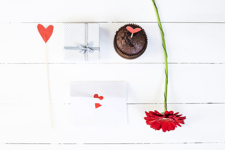 St. Valentines Day concept. Holiday decoration. A gift, a red flower, a paper heart on a stick, a chocolate muffin and a love letter Stock Photo