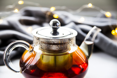 a teapot with black tea next to a gray scarf and Christmas garland. Winter concept