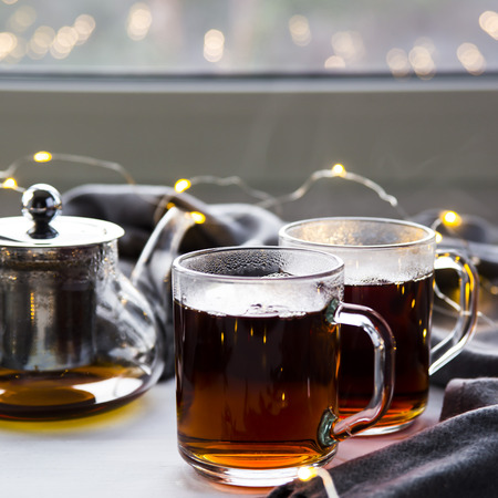 Black tea in a transparent teapot and cups by the window. Winter concept