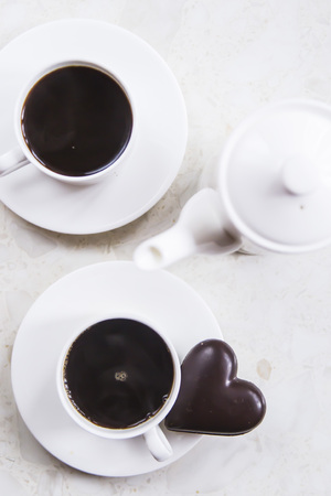 white kettle and cups on white table with chocolate heart. Minimalism and Valentines Day