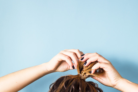 The woman straightens the disheveled bun on her head with her hands with a black manicure. Dark hair is tied with a transparent spiral elastic band. Modern fast hairstyle. Blue background. Copyspace Stockfoto