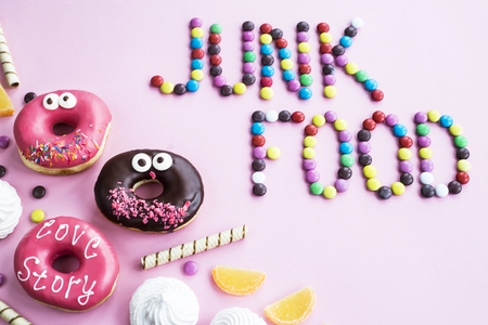 The phrase Junk food is lined with chocolate glazed balls on a pink background. Next to donuts, marmalade, chocolate sticks and meringue. Unhealthy food concept. Top view