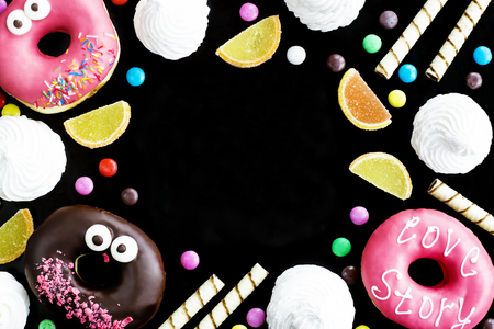 Junk food. Donuts, marmalade, chocolate sticks and balls, and meringue on a black background. Unhealthy food concept. Background with copyspace