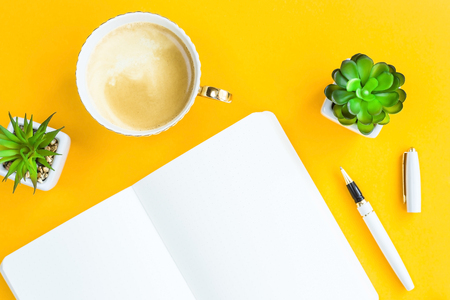 Workplace with bklonotom, pen, cup of coffee and green whiskers in white pots. On a bright yellow background. Top view. Flat lay Standard-Bild