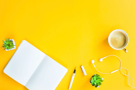 Workplace with a biclone, pen, headphones, a cup of coffee and green whiskers in white pots. The working space of a freelancer, journalist, writer, modern worker. Bright yellow background. Top view. Flat lay. Copyspace Stock Photo
