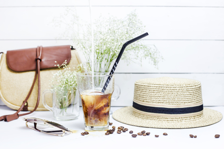 Milk is poured into a glass with a cold coffee with ice, which stands on a white table among the female summer accessories. Next to the dry bouquet gypsophila. Summer relax concept