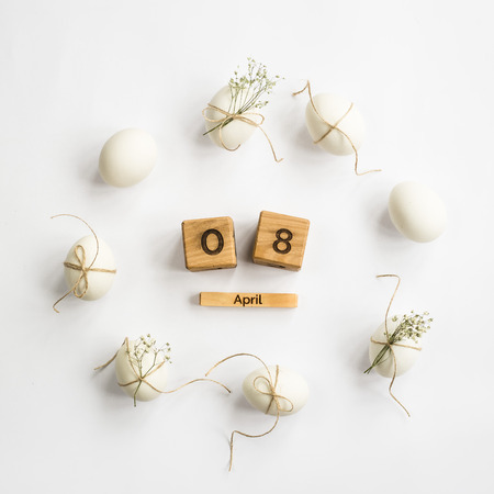 Easter white eggs are minimalistically decorated with twine and gypsophila. With a wooden calendar. 08 April 2018. Easter. Top view, flat lay