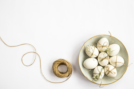 Easter eggs are minimalistically decorated with twine and gypsophila flowers in a blue round plate next to a skein of twine on a white background. Top view, flat lay. Copyspace