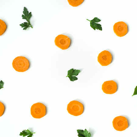 Bright round ringlets of carrots and green twigs of parsley on a white background. Healthy food concept. Top view, flat lay Stock Photo