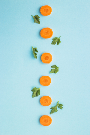 Bright round ringlets of carrots with green parsley sprigs on a blue background. Top view, flat lay