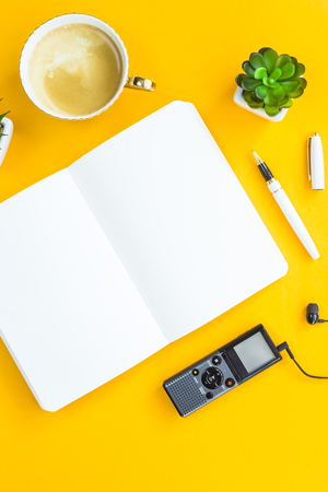 Workplace of the journalist with a dictaphone, headphones, a notebook, a pen and green plants on a yellow background. Flat lay, top view Stock Photo