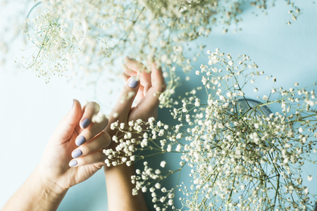Blue manicure on female nails on a blue background next to the flowers of gypsophila. Trend for gentle pastel colors. Beauty and personal care Banque d'images