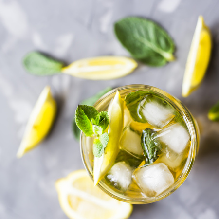 A glass glass with a cold tea with ice, mint and lemon on a gray concrete background. Summer cooling drink. Top view, flat lay