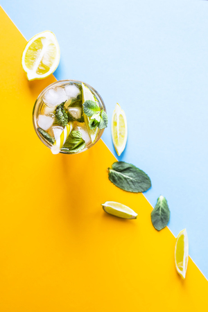 Ice tea with ice, lemon and mint on a combined colored yellow and blue background. Summer cold drink cocktail. Top view, flat lay Stock Photo