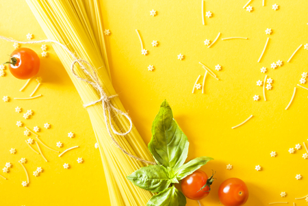 Dry spaghetti on a yellow background next to cherry tomatoes and a basil leaf. Top view; flat lay