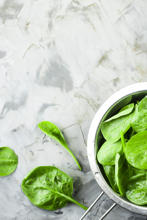 Washed spinach in a metal colander on a gray background. Fresh green leaves for cooking healthy dishes Archivio Fotografico