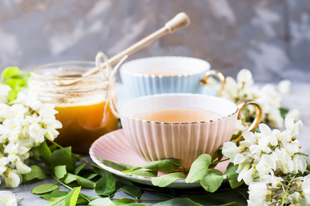 Vintage cups with tea next to a jar of honey and acacia on a gray table. Tea with natural sweetener honey Stock Photo