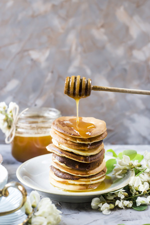 A pile of fritters next to a cup of tea and a jar of honey on a gray background among the flowers of the acacia. Spring delicious breakfast