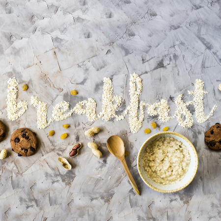 The word breakfast is written on a gray background of oatmeal. Next to a bowl of ready-made oatmeal, spoon, nuts, raisins and chocolate biscuits. Minimalism. Top view, flat lay