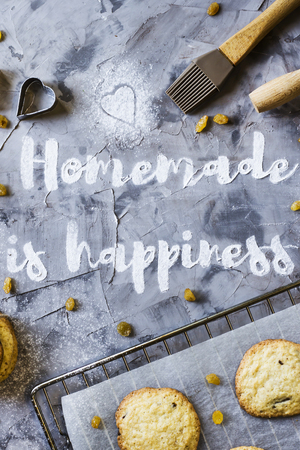 Word Homemade is written on a gray concrete background of flour. Next to the baking sheet with biscuits, shapes and rolling-pin. Homemade pastry concept. Top view, flat lay