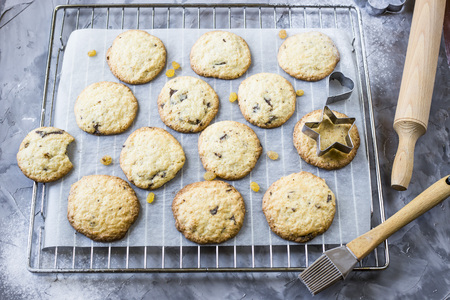 Homemade oatmeal cookies with chocolate chips on a gray kitchen table among accessories for baking Stock Photo