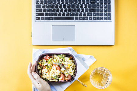 Vegetable salad with macaroni bowls with cheese in a container for lunch at the office workplace near the laptop. Top view, flat lay