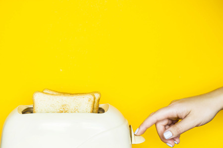 Toasted bread sticks out of the toaster on a yellow background. Female hand switch on the toaster