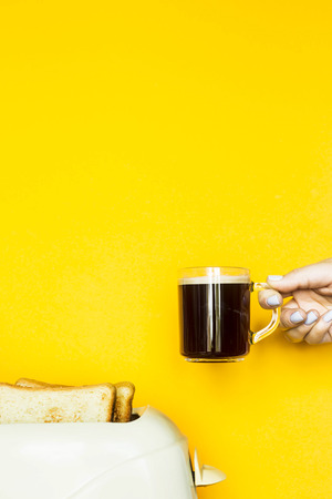 Toasted bread sticks out of the toaster on a yellow background. A female hand holds a cup of coffee. Breakfast concept