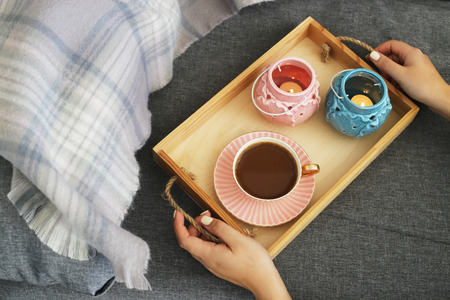 A woman is holding a cup of coffee and milk on a wooden tray with pink and turquoise candlesticks on a gray cozy sofa with a checkered powder rug. Interior and home cosiness concept. Top view