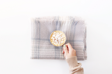 Warm delicate powdery checkered scarf folded rectangle on a white background with a cup of cocoa in a female hand. Winter days concept. Top view, flat lay